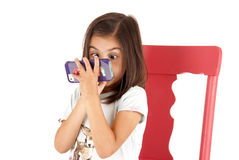 Girl with wide eyed expression playing game on pho Stock Photos