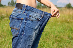 Girl in wide jeans. Girl with a beautiful belly holding his hand wide jeans stock photography