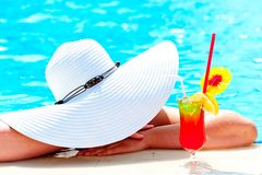 Girl in a wide white hat resting in the pool stock photography