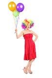 Girl with wig holding a bunch of balloons Stock Photo