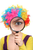 Girl in wig looking through magnifying glass Royalty Free Stock Images