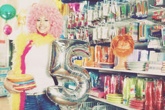 Girl in a wig shows things for a party. Cheerful girl in a wig shows things for a party in a store Stock Photo