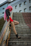 The girl in the wig on the stairs Stock Images