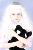 Girl in a wig with a toy Royalty Free Stock Photos
