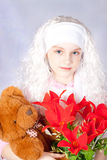 Girl in a wig with a toy Stock Images