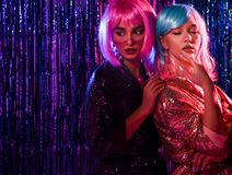 Girl in wigs and stylish glamorous dresses with sequins, in the neon light of a disco. Celebrate, have fun, celebrate something stock photos