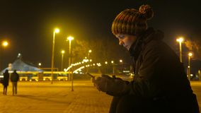 Girl wih a phone in her hands. Chatting on a night city background. 4K video. stock video footage