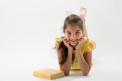 Girl wiht book. Girl lying on the floor, a book next to her Royalty Free Stock Photography