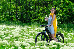 Girl among the wild flowers on a bike with bottle of water Stock Images