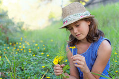Girl in wild flowers field. Cute young girl wearing straw hat and denim dress, sitting in a field of yellow wild flowers and looking pensive Royalty Free Stock Photo
