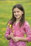 Girl (7-9) with wild flowers in field, smiling, portrait Stock Images