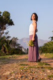 Girl with wildflowers on gravel road. Long skirt stock images