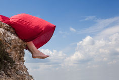 Girl and wind. Girl sitting on the edge of a mountain royalty free stock photo