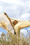 The girl and a wind. Girl in the middle of a wheaten field Royalty Free Stock Image