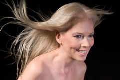 Girl In Wind. Close up portrait of an attractive smiling female with hair blowing in the wind Royalty Free Stock Photos