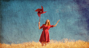 Girl with wind turbine. At field Royalty Free Stock Image