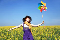 Girl with wind turbine at rape field. Stock Images