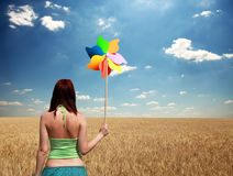 Girl with wind turbine at wheat field Stock Photos