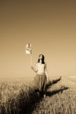 Girl with wind turbine at wheat field. Photo in age yellow style #1 Stock Image