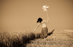 Girl with wind turbine at wheat field Stock Photo