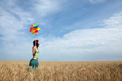 Girl with wind turbine at wheat field. View from corner Stock Photo