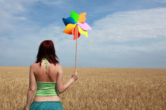 Girl with wind turbine at wheat field. View from back side Royalty Free Stock Photos