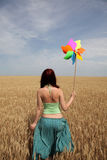 Girl with wind turbine at wheat field Royalty Free Stock Photography