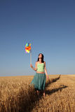 Girl with wind turbine at wheat field. Girl with wind turbine walking at wheat field. View form front. Photo 2 Stock Photos