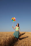 Girl with wind turbine at wheat field. Girl with wind turbine walking at wheat field. View form front. Photo 3 Royalty Free Stock Images