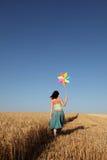 Girl with wind turbine at wheat field. Girl with wind turbine walking at wheat field. Photo 1 Royalty Free Stock Photo