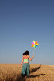 Girl with wind turbine at wheat field. Girl with wind turbine walking at wheat field. View form back side. Photo 4 Royalty Free Stock Images
