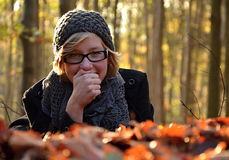 Girl in windfall leaves Stock Photography