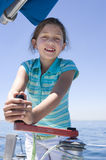 Girl (8-10) winding rope pulley of boat rigging on deck of sailing boat out at sea, smiling, front view, portrait Stock Photo
