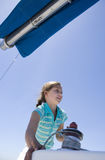 Girl (8-10) winding rope pulley of boat rigging on deck of sailing boat out at sea, smiling, low angle view Stock Image