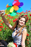 Girl with windmill in poppy field Stock Image