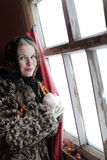 Girl at the window. Girl in a fur coat in the window. Winter Village. Canon 5Dmark2 Stock Images