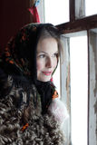 Girl at the window. Girl in a fur coat in the window. Winter Village. Canon 5Dmark2 Royalty Free Stock Photography