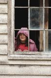 Girl at the window. A girl looks out an old shed window royalty free stock image