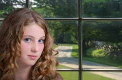 Girl by Window. Female standing by a window with a Mona Lisa smile Stock Images