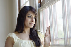 Girl at the window. A young Asian woman smiling as she is looking out through a window Royalty Free Stock Image