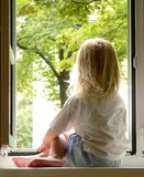 Girl in the window Royalty Free Stock Image