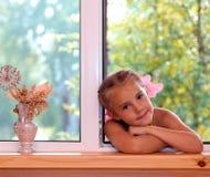 A girl in the window. Stock Photos