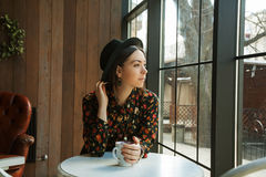 The girl at the window. Beautiful woman in hat drinking coffee in the morning sitting by the window. view from inside Stock Image
