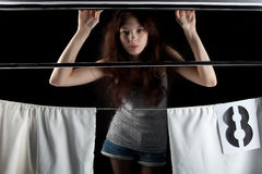 Girl in the window on black background with white curtains Royalty Free Stock Photography