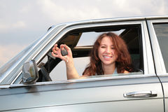 Girl in window of car with  key Stock Photo