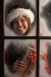 Girl in Window with Christmas Present Royalty Free Stock Photo