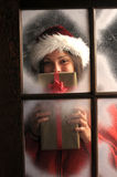 Girl in Window with Christmas Present Royalty Free Stock Image