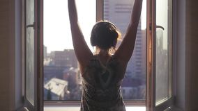 The girl at the window, hands up in the glad spring sun. Listening to music on headphones. slow motion. 1920x1080 stock footage