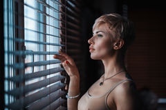 Girl at the window with jalousie. A beautiful girl at the window of the house looks out between the blinds by lifting one of them Royalty Free Stock Photography