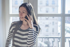 Girl at the window talking on the phone at home in morning sunlight. Copyspace right Royalty Free Stock Photo